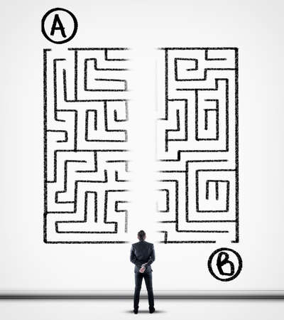 Thoughtful businessman solving a maze using a shortcut. Maze drawn on a white wall. Point a to point b.