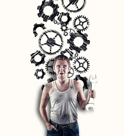 Excited mechanic in standing in front of a white wall drawn with engine gear wheels.