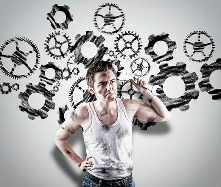 Confused mechanic holding a wrench in front of a white wall. Wall drawn with a engine wheels gear.