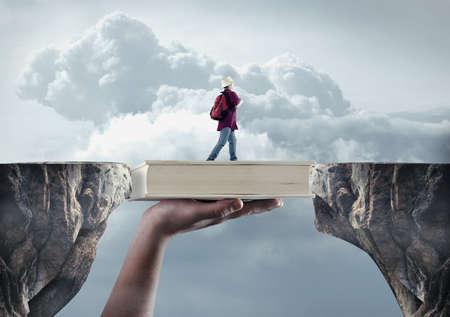 Le jeune homme passe d'un sommet à l'autre sur un livre. Le concept de bourse. Banque d'images