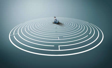 Thoughtful man sitting in the middle of a round maze.