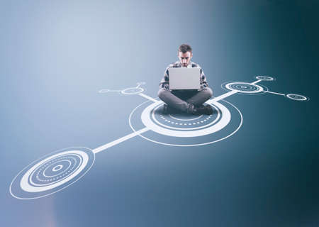 Man working on laptop in the middle of a network .