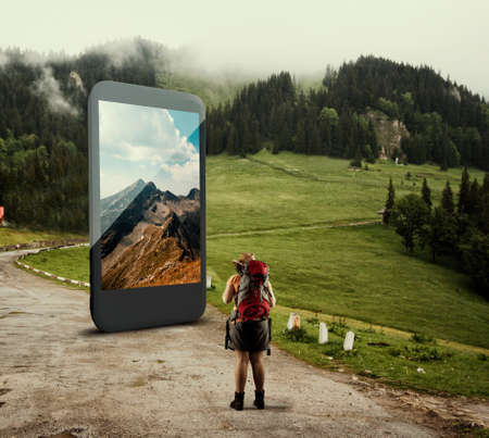 Traveller standing on a road in front of a big smartphone. The concept of booking online for travel.