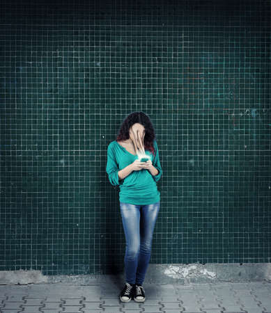 Woman using smartphone against a wall. The concept of phone addiction. Face absorbed by the phone. Stock Photo