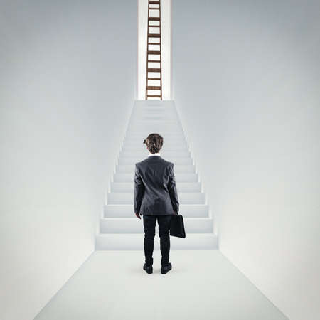 Businessman standing in a hallway in front of the stairs . Ladder on top of the stairs. The concept of success .