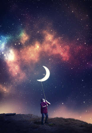 Young man pull the moon towards him with a rope in the middle of the night. The concept of accomplish his dreams.