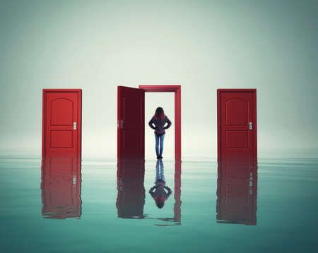 Woman on water in front of different doors. The concept of choosing the right way Stock Photo