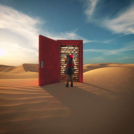 Traveller with a backpack in the desert in front of a opened door with a brick wall. The concept of wrong choice. Stock Photo