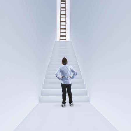 Homme d'affaires debout dans un couloir devant les escaliers. Échelle en haut de l'escalier. Le concept de réussite.