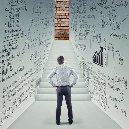 Hombre de negocios en una sala tratando de resolver problemas matemáticos dibujados en las paredes. Escaleras que conducen a una puerta bloqueada.