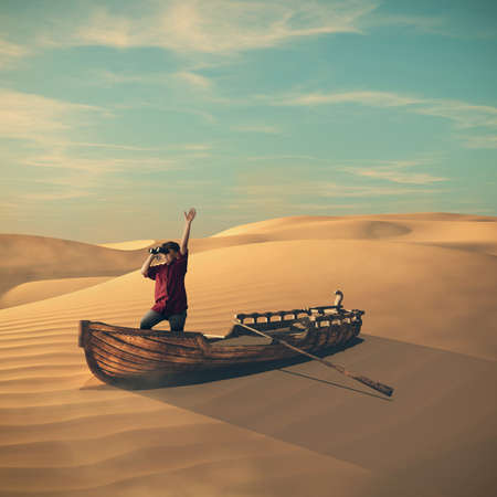 Young traveller standing on a boat in the desert , looking through binocular. The concept of global warming and climate change. Stock Photo