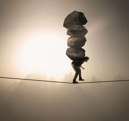 Man carries a stack of big rocks while balancing on a rope at high altitude . Stock Photo