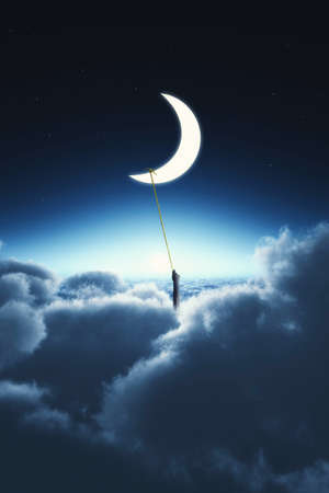 Hand holding a rope tied to the moon, above clouds Stock Photo