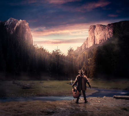 Cowboy holding a guitar in the nature surrounded by mountains and trees. Stock Photo