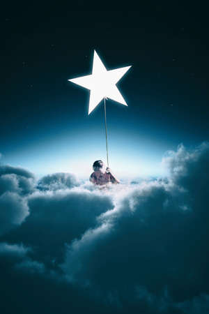 Man climbing on a rope to a star, during night above clouds. Stock Photo
