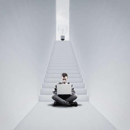 Homme travaillant sur ordinateur portable sur son idée. Escalier vers une ampoule. Le concept de travailler sur des affaires personnelles.