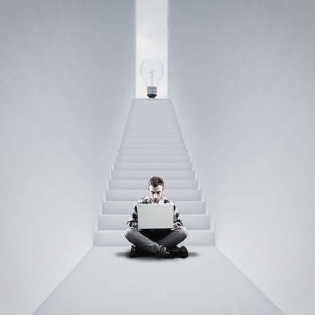 Man working on laptop on his idea. Stairway to a lightbulb . The concept of working on personal business. Stock Photo