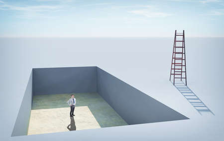 Businessman standing in a  pit , looking up to a ladder. Stock Photo
