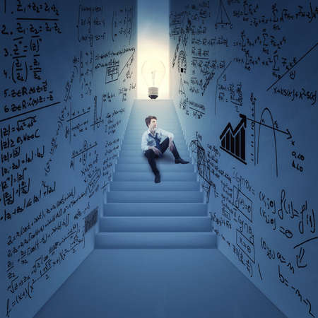 Man sits on stairs in a hallway to a lightbulb with walls drawn with math formulas . The concept of business idea.