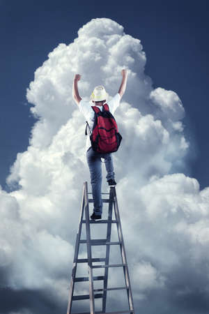 Young man on top of a ladder rising his hands up in front of a big cloud. The concept of success.