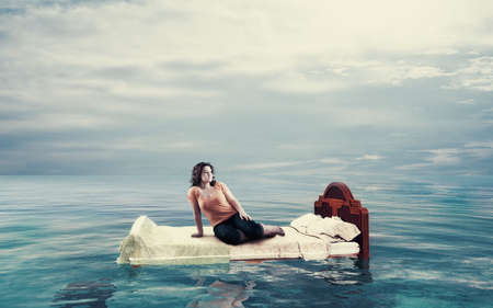 Woman sitting on a bed floating in the ocean.