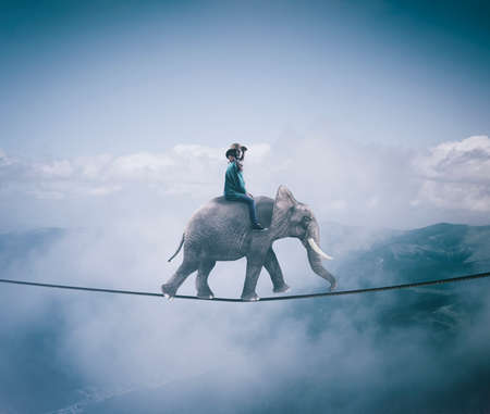 Young woman riding an elephant on a rope at high altitude, above clouds and mountains. Stock Photo