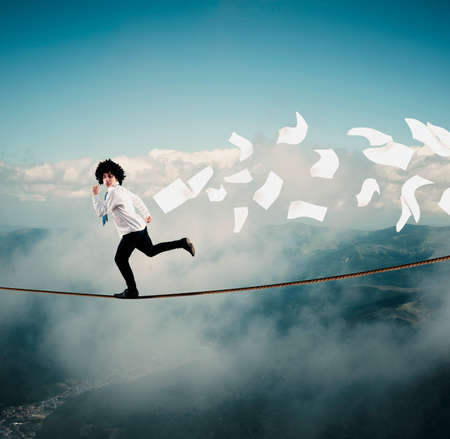 Young man runs away from bills on a rope, above clouds and mountains. The concept of getting rid of debts and bills. Stock Photo