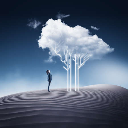 Woman looking up to a circuit board tree and a cloud above, in the desert. Stock Photo