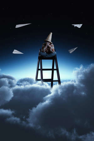 Young man sitting on top of a ladder above clouds , surrounded by paper air planes. Stock Photo