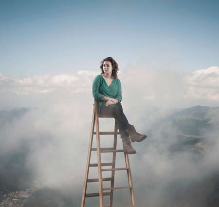Woman sitting on top of a ladder above clouds and mountains.