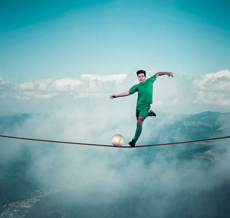 Football player shoots the ball on a rope , above clouds and mountains. Stock Photo