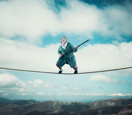Pretty young woman pretending to play guitar with the broom and dressed with a gown . Standing on a rope at high altitude above mountains and clouds.