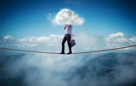 Businessman walks on a rope at high altitude above mountains and clouds . Head covered by a cloud.
