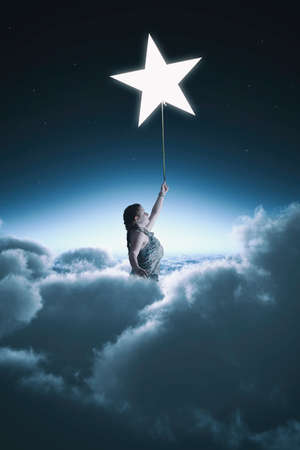 Woman rising up above the clouds holding a star.