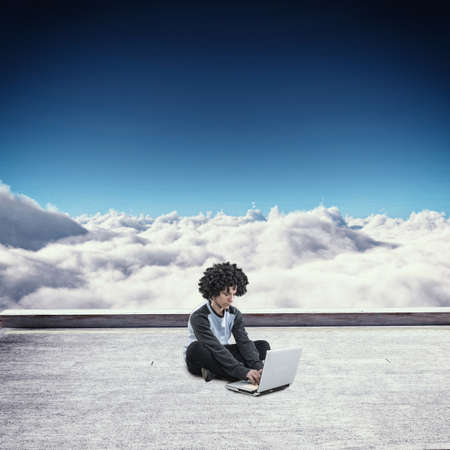 Young man working on laptop at high alititude above clouds. Archivio Fotografico
