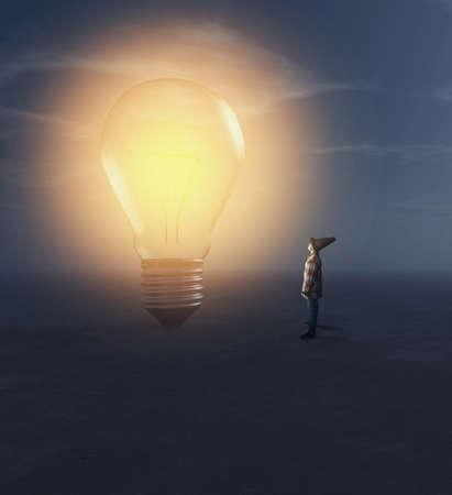 Jeune homme regardant une ampoule allumée la nuit. Banque d'images