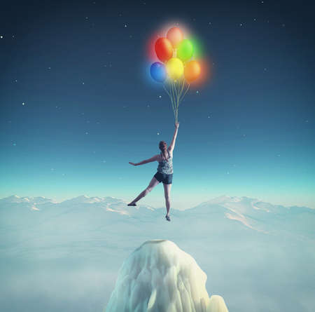 Woman flying with colorful balloons in the night. The concept of accomplished dreams. Stock Photo