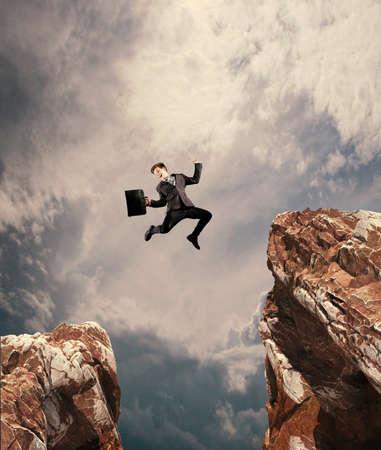 Imagen del joven empresario saltando por encima de la brecha. El concepto de promoción