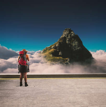 Traveler stands on terrace above clouds looking at a mountain peak