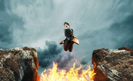 Geschäftsmann springt über ein Feuer zwischen einer Lücke von zwei Berggipfeln.