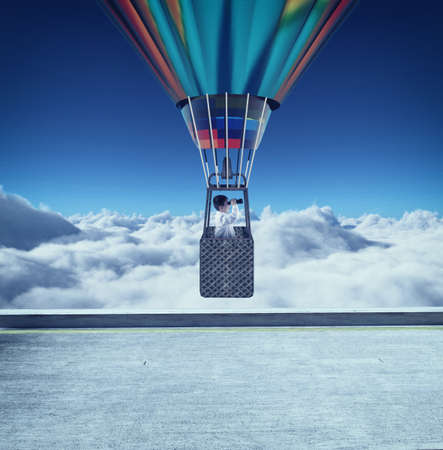 Young man flying with hot air balloon and looking through binoculars above clouds. Banque d'images