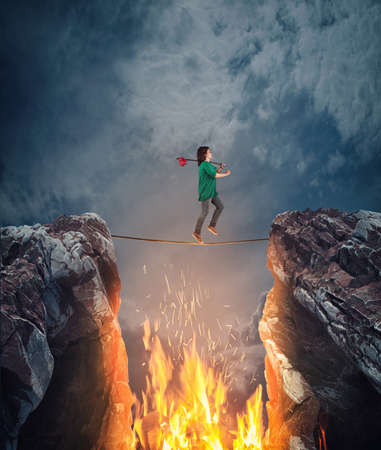 Surreal challenge overcome . Woman conquering obstacle balancing on slackline rope above a gap with flames between two mountain peaks.Risk taking , success concept. Stock fotó