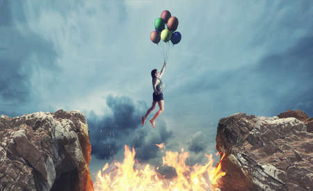 Woman hold balloons and jumps over a fire between a gap of two mountain peaks.