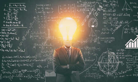 Student with lit light bulb as a head solving math problem drawn on blackboard. Stock Photo