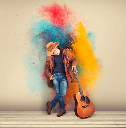 Cowboy with a acoustic guitar against a colorful painted wall. Powder explosion .