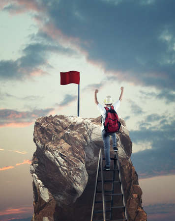 Young man on top of a ladder rising his hands up in front of mountain peak with a red flag.