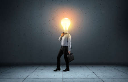 Businessman with a lit lightbulb instead of head. Stock fotó