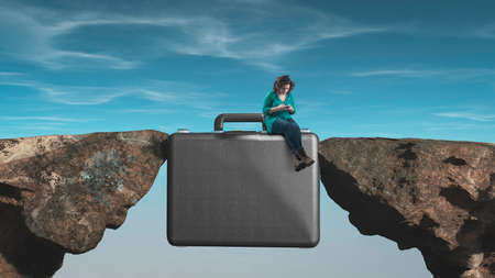 Woman working on smartphone on a suitcase between two rocks. Influencer concept