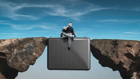 Businessman sitting on a briefcase between two rocks. Application for new job.