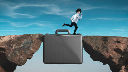 Businessman running on a suitcase between two rocks.